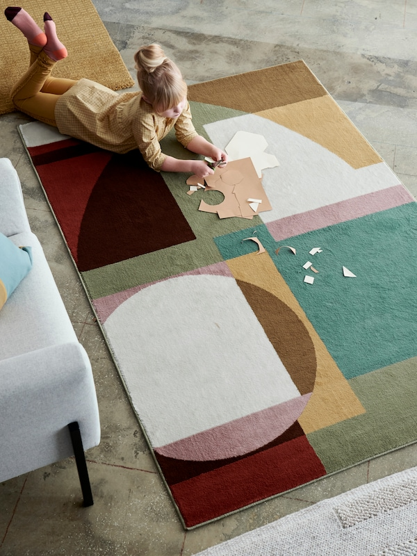 A large, multicoloured STENMÄTARE rug with low pile and a bold, geometrical pattern and a girl cutting paper.