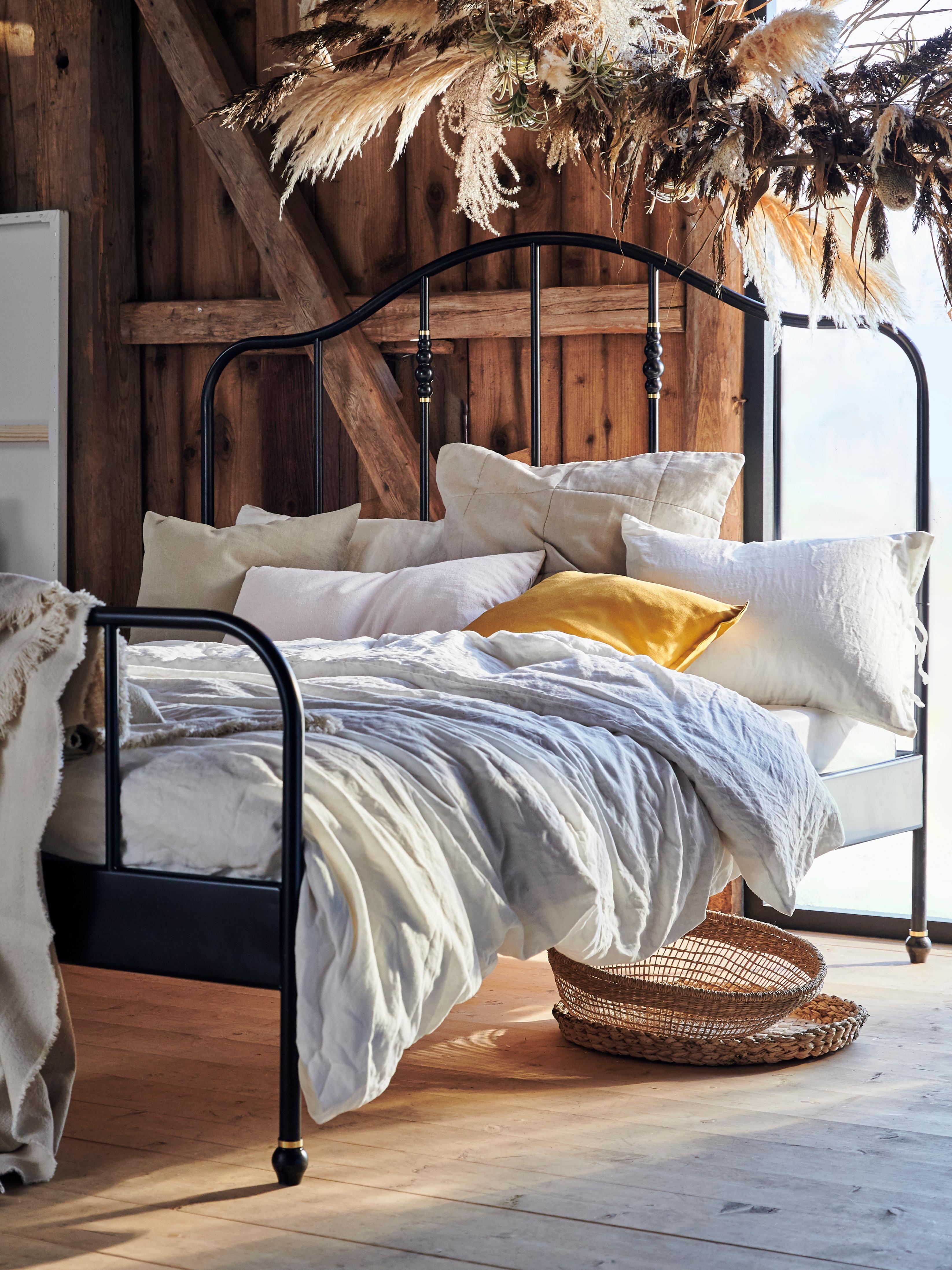 Estrutura de cama SAGSTUA com cabeceira alta, num quarto claro, com um toque natural, parede e chão de madeira.