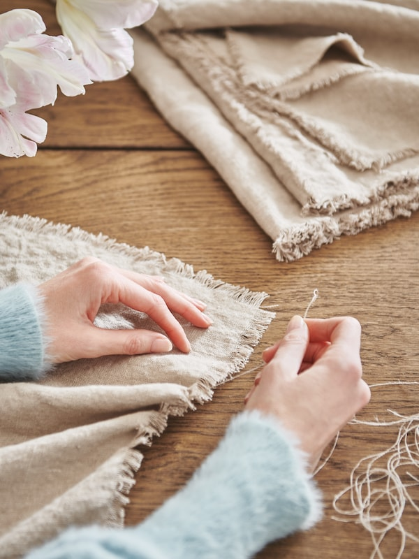 A pair of hands decoratively fraying a length of natural-colour AINA fabric by pulling threads from its edges.