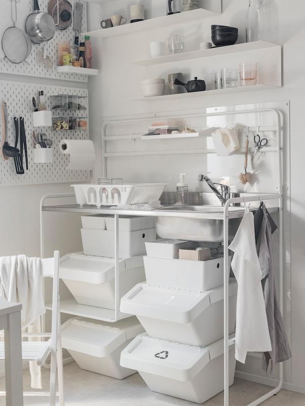 O mini-bucătărie SUNNERSTA cu cutii de depozitare dedesubt, cu unelte de bucătărie și tigăi suspendate de plăcile cu agățători SKÅDIS.