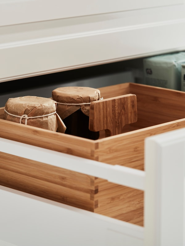A pulled-out kitchen drawer in traditional style, two jars with paper wrapped around the top in a VARIERA box in bamboo.