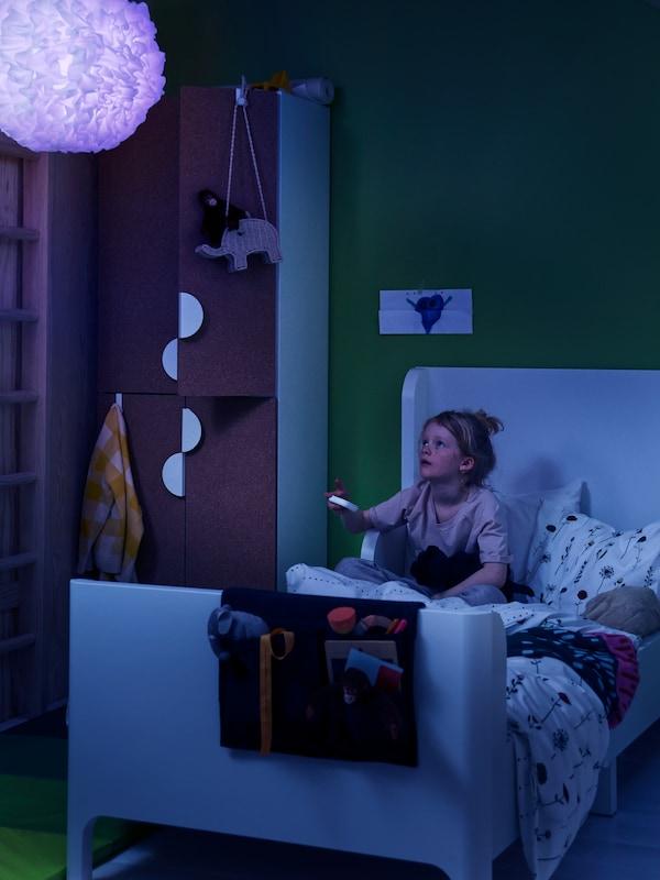 Кут невеликого письмового столу з TRÅDFRI ТРОДФРІ блоком керування, світлодіодною підсвіткою та склянкою, в якій стоять олівці та пір'я.
