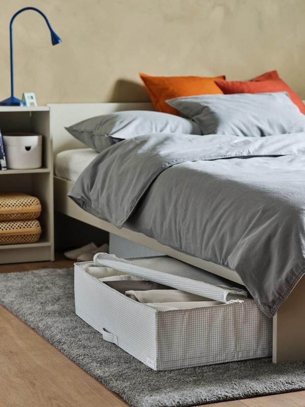 Sengestel med sengegavl og sengebord i lys beige, hvid/grå opbevaringstaske og en LED-skrivebordslampe.