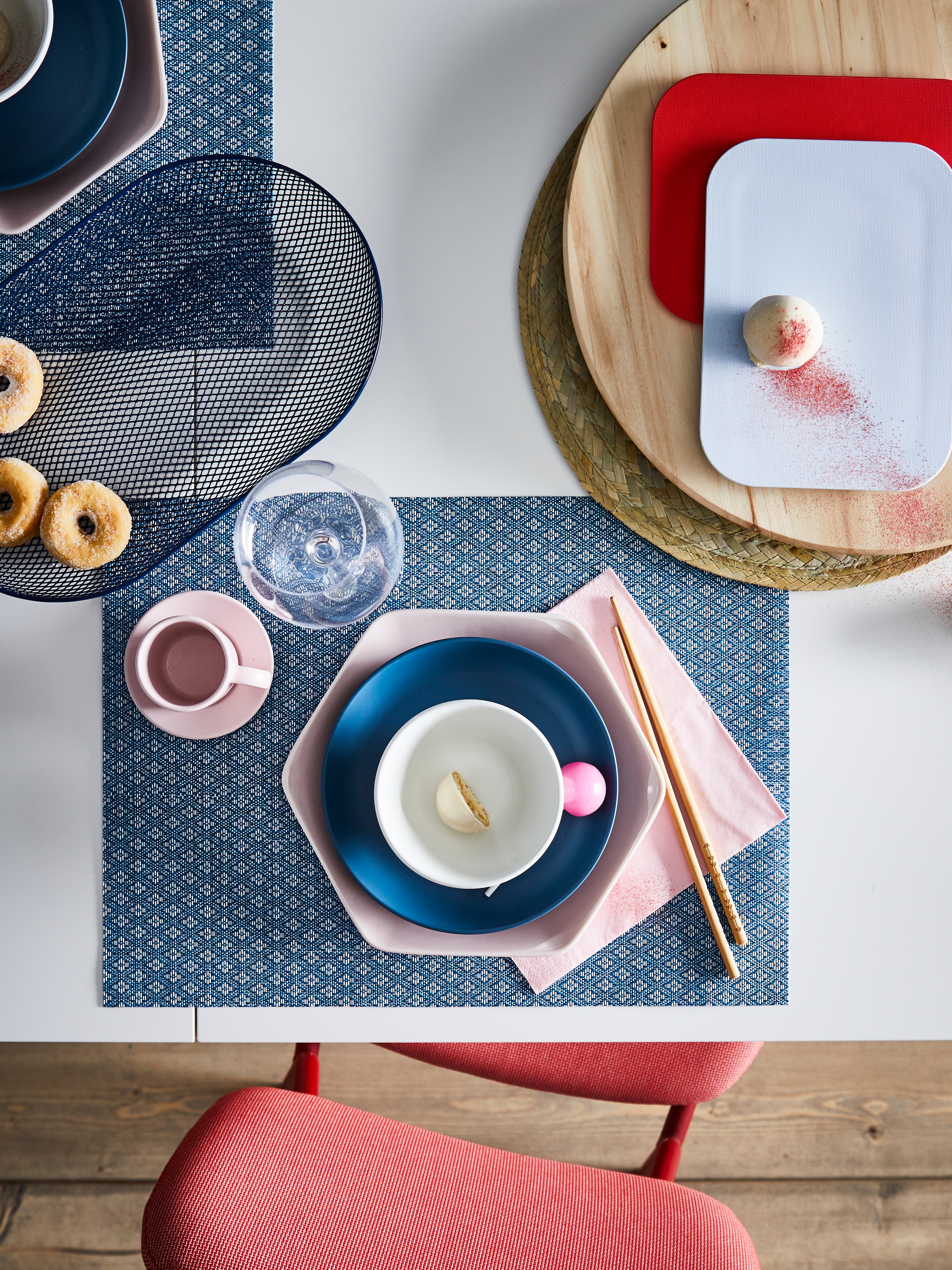 GALLRA place mat in blue, with blue and pink bowls on a table, chop sticks and various other tableware items.