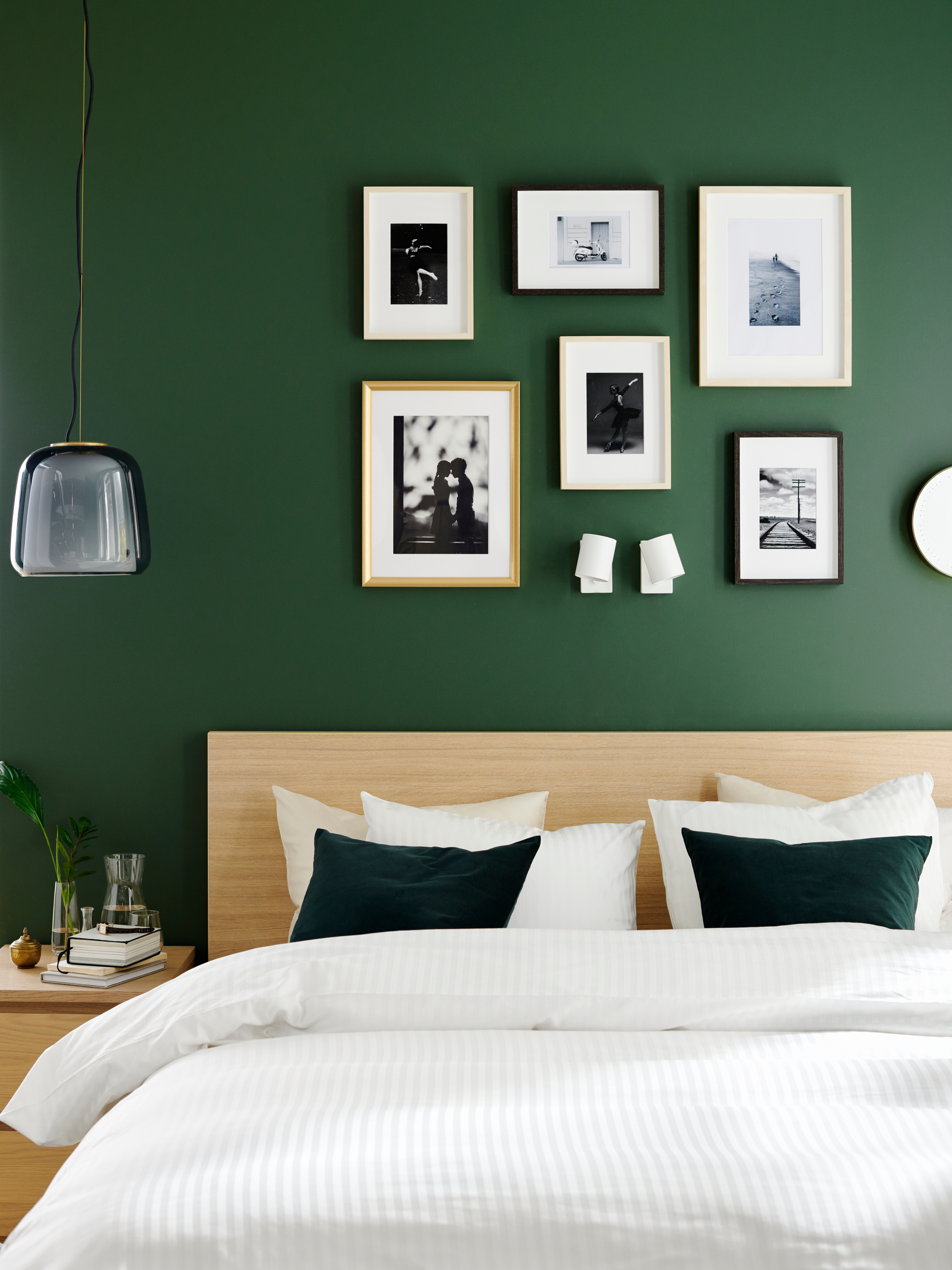 A bed with an oak veneer headboard, in front of a green wall full with pictures, some of which have a SILVERHÖJDEN frame.