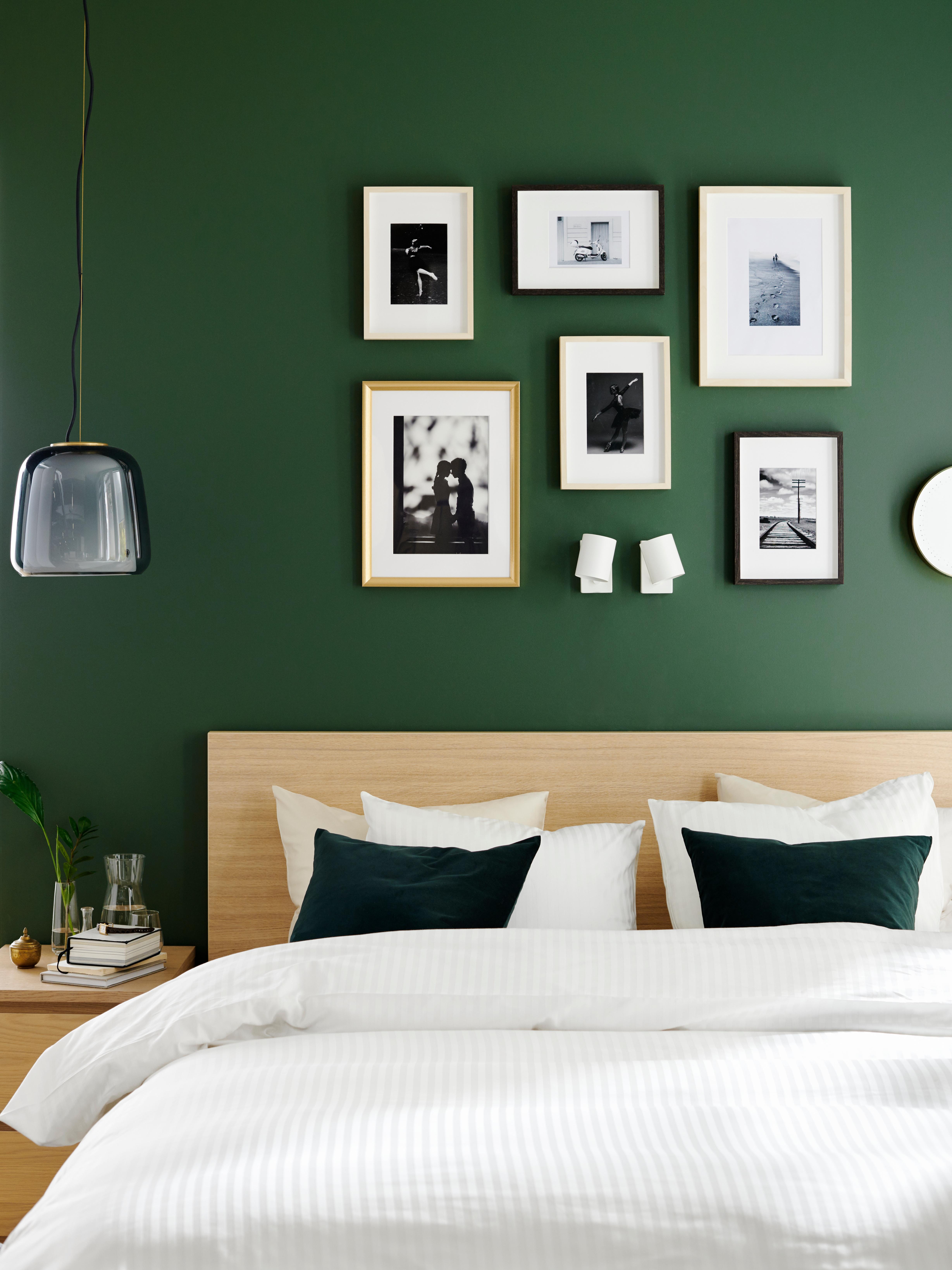 Krevet s uzglavljem od hrastovog furnira, ispred zelenog zida punog slika, od kojih neke imaju SILVERHÖJDEN okvir.