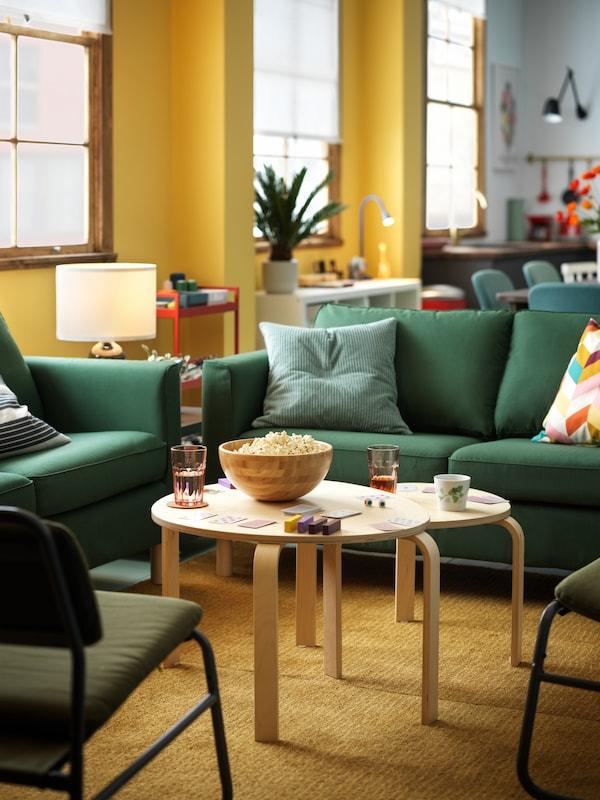 Sala de paredes amarelas com dois dofás verdes e duas mesas de centro no meio em bétula.