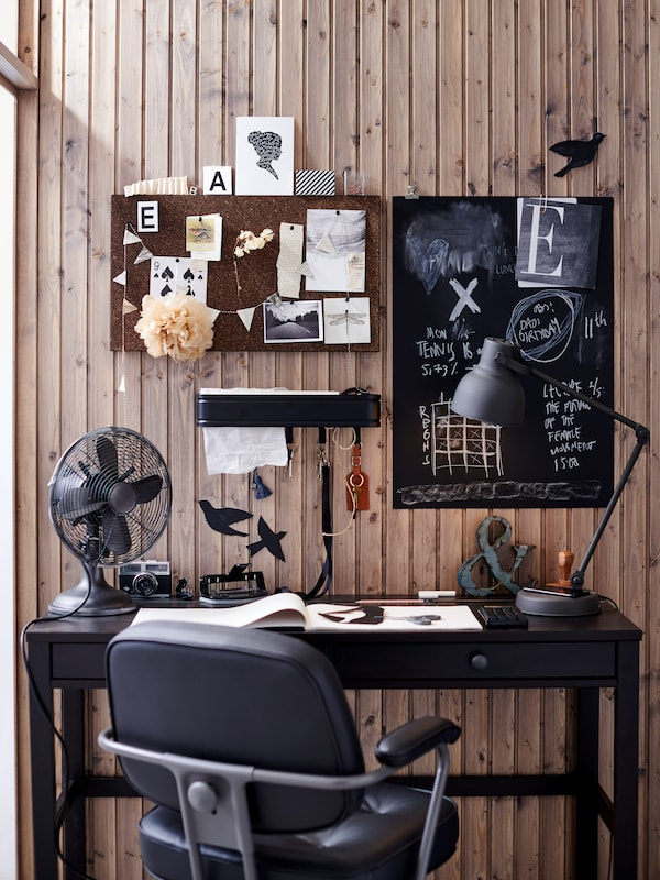 Workspace in dark colours. The wall above is covered with SVENSÅS and SÄVSTA memo boards, a LILLASJÖN shelf and decorations.