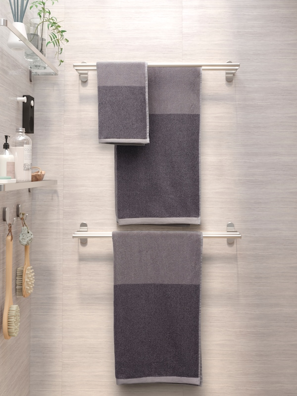 Three grey towels hanging from two BROGRUND towel rails. On the wall to the left are glass shelves with shower products.