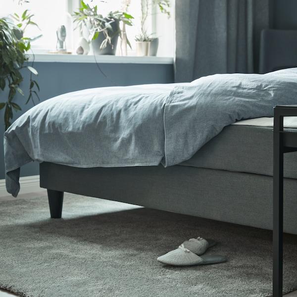 Divano letto SÄBÖVIK grigio con biancheria da letto KOPPARBLAD di fronte a una finestra con molte piante sul davanzale.
