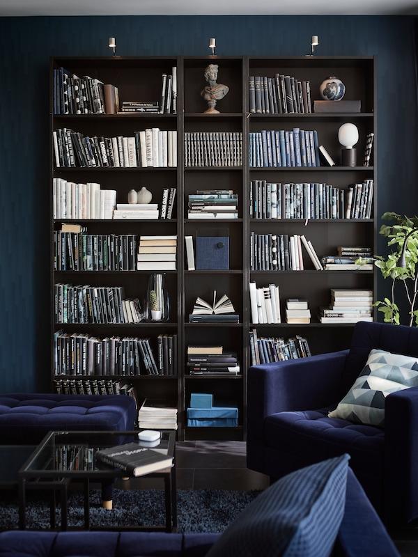 Vmodrej obývacej izbe stojí čiernohnedá knižnica BILLY smnožstvom kníh aniekoľkými ďalšími predmetmi. Vpopredí je modré kreslo.