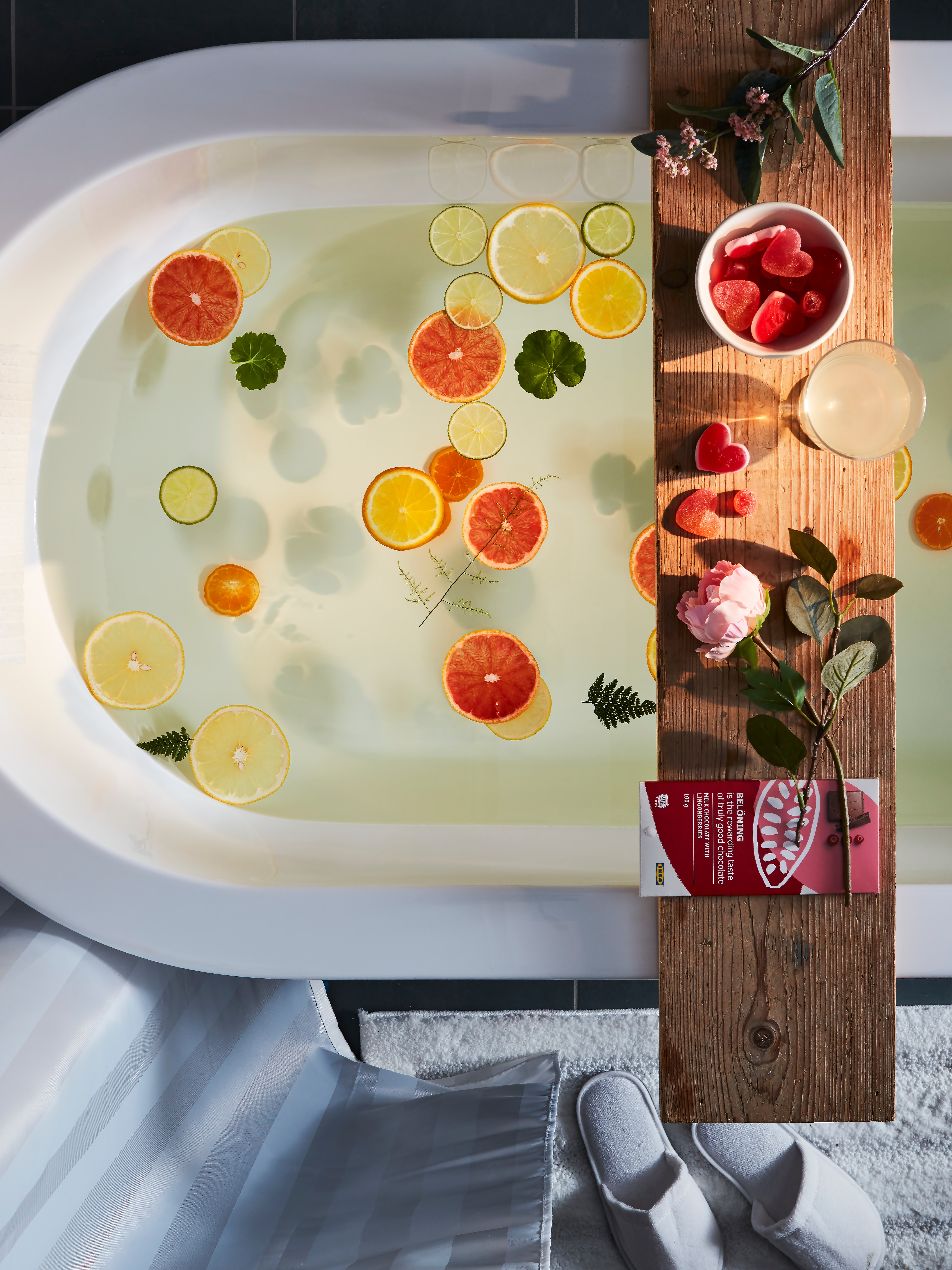 An aerial view of a filled bathtub that has a shelf across it, holding a BELÖNING milk chocolate tablet with lingonberries.