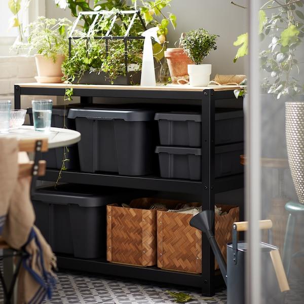 Several dark gray bins sitting on a black storage rack with plants on top.