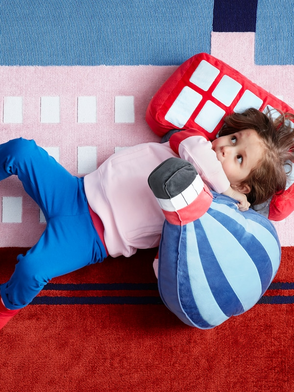 A child lies on an UPPTÅG rug with an UPPTÅG cushion shaped like a bus and another one shaped like a hot air balloon.