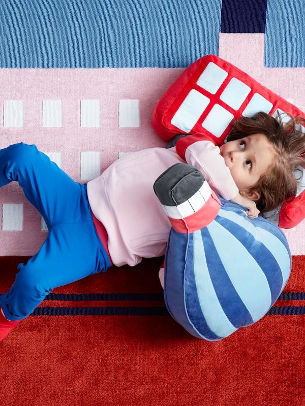 Una bambina su un tappeto UPPTÅG con un cuscino UPPTÅG a forma di autobus e un altro a forma di mongolfiera.