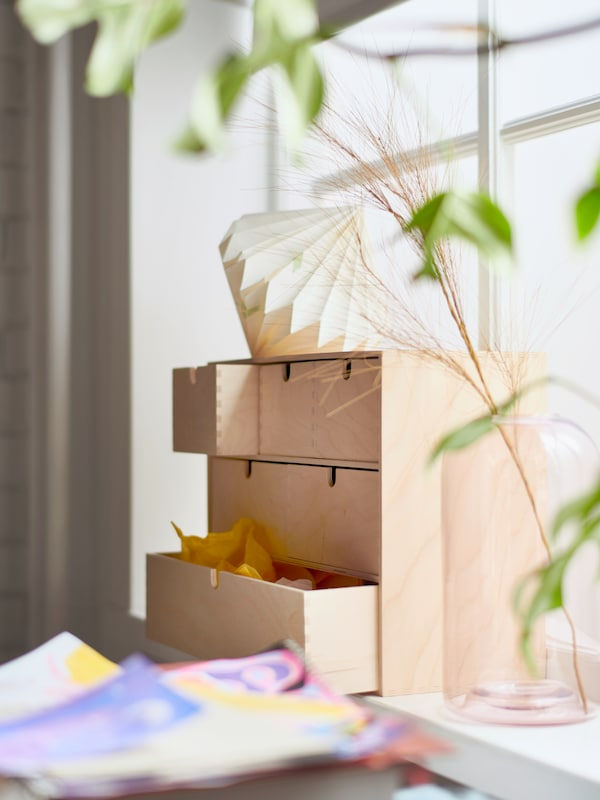 Une commode miniature MOPPE faite en bouleau contreplaqué située sur le rebord d'une fenêtre, quelques dessins et un vase en verre contenant une branche.