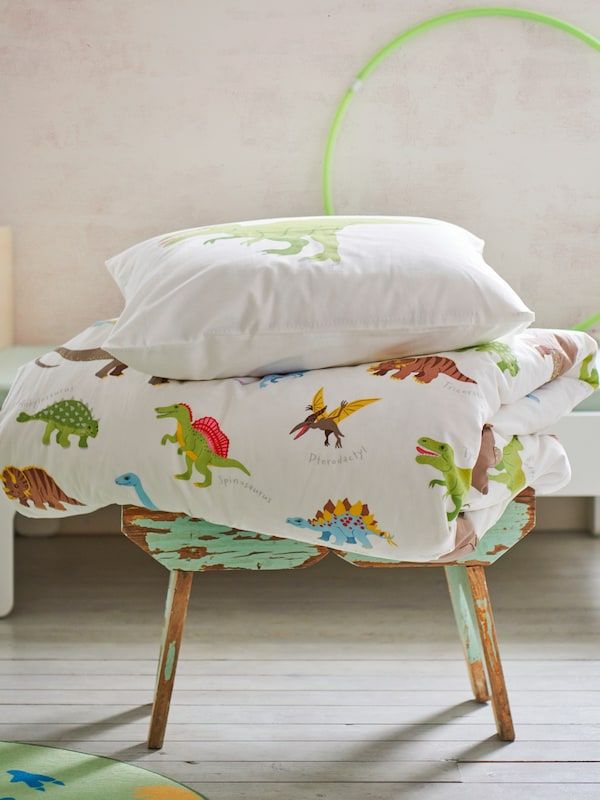 A duvet and pillow in a JÄTTELIK quilt cover and pillowcase sit on a stool near a bed in a child's bedroom.