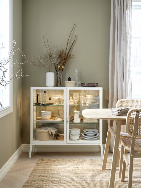 A white glass-door cabinet with integrated lighting filled with tableware stands in the corner of a dining room.