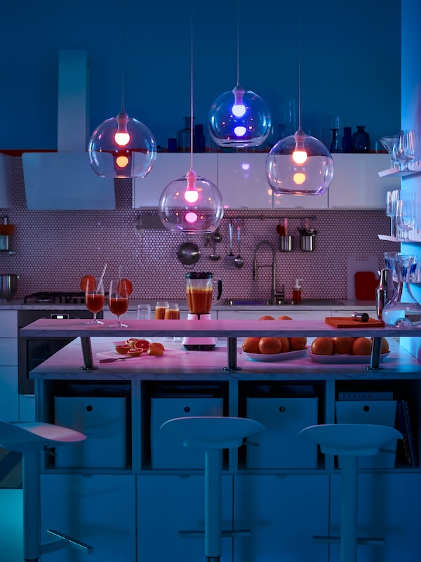 Four JAKOBSBYN pendant lamps with bulbs with different colors hang down over a kitchen countertop and dining area.