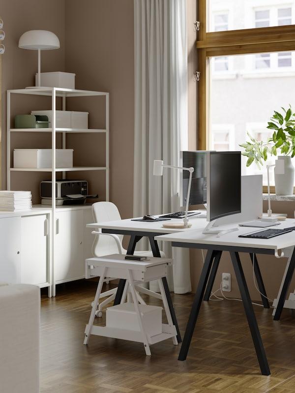 Es ist ein Wohnzimmer mit einem Drehstuhl, Leuchten und zwei TROTTEN Schreibtischen zu sehen, die sich gegenüberstehen. Dazwischen befindet sich eine Notiztafel.