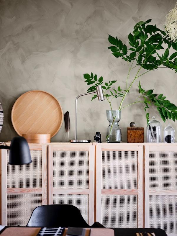 Une étagère IVAR avec des portes en bambou, combinée avec de beaux accessoires en bois, des vases en verre et des lumières fonctionnelles sur le dessus de l'unité.