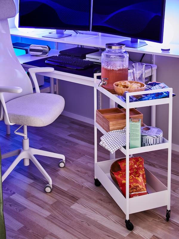 Židle před psacím stolem se dvěma monitory, a tříposchoďový vozík s občerstvením a krabicemi.