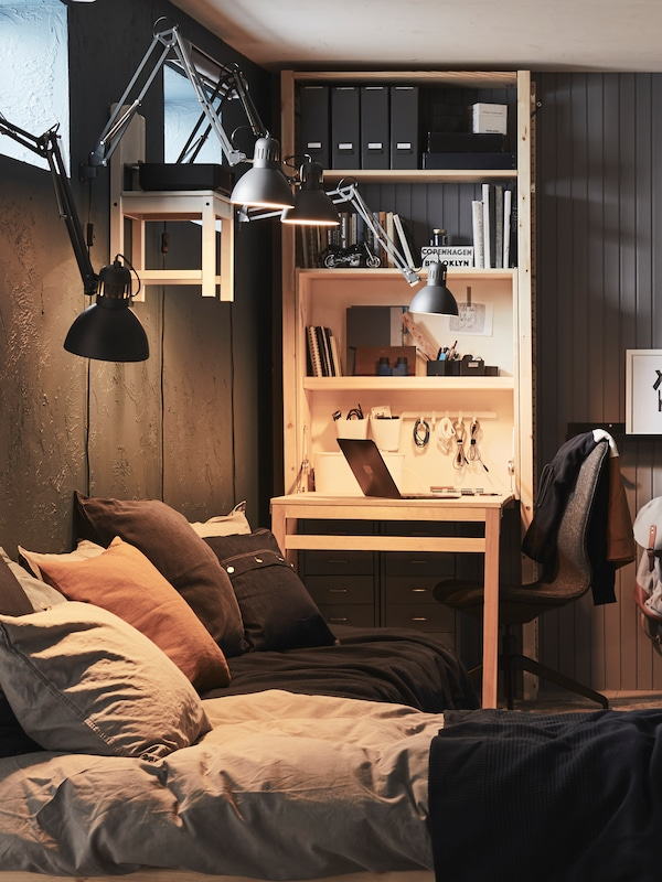 Four, dark grey, TERTIAL work lamps fixed to a wall shine down onto a bed and a pine, IVAR storage unit with foldable table.