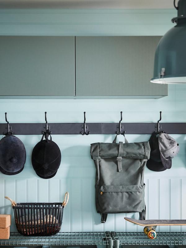 Två PINNIG hängare med 3 krokar där det hänger en ryggsäck och kepsar har monterats på en grön vägg under BESTÅ väggskåp.