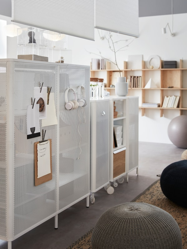 White storage units with earphones and clipboards hanging from them, items placed on top and wooden shelves behind.