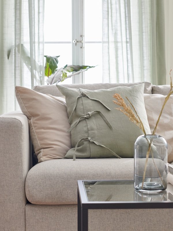 Beige and light green cushion in a beige VIMLE sofa in front of a table.