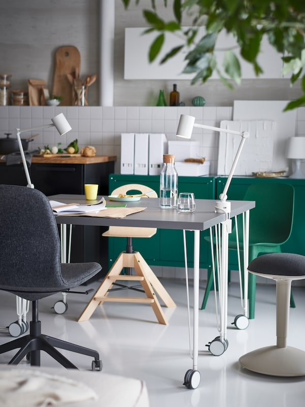 Two grey tables made from dark grey LAGKAPTEN table tops and white KRILLE legs with castors, work lamps and various chairs.
