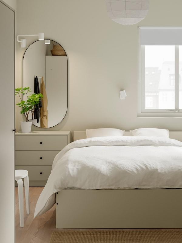 Un corp cu ușă de sticlă RUDSTA, de culoare turcoaz, plin de ornamente albe, într-un spațiu neutru, minimalist.