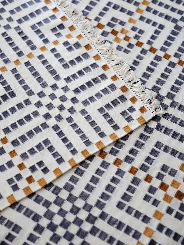 Alfombra plana VAMDRUP con un estampado tradicional de varios colores sobre otra alfombra VAMDRUP.