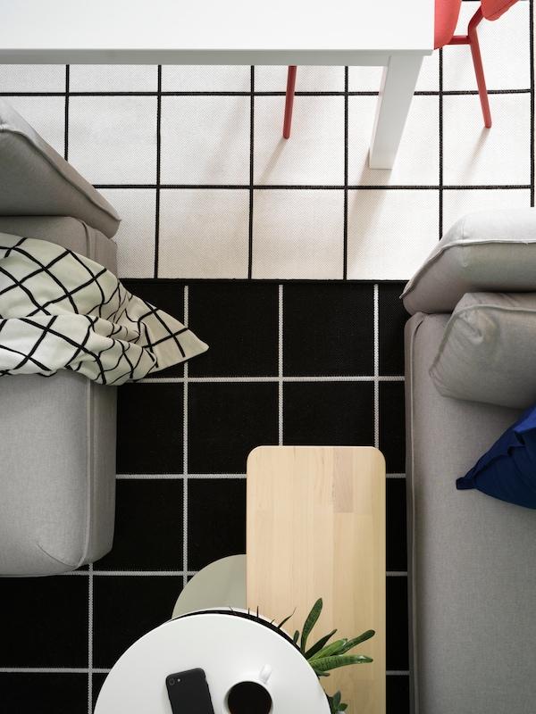 Vue du dessus de deux tapis à motifs carrés noir et blanc, une table de salle à manger blanche et un canapé gris.