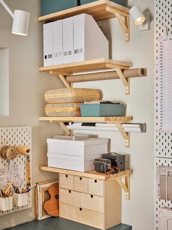 رفوف مع حاملات وحافظات مجلات وخزانة ذات أدراج صغيرة ولوحات تعليق بيضاء وصناديق تخزين بأغطية.