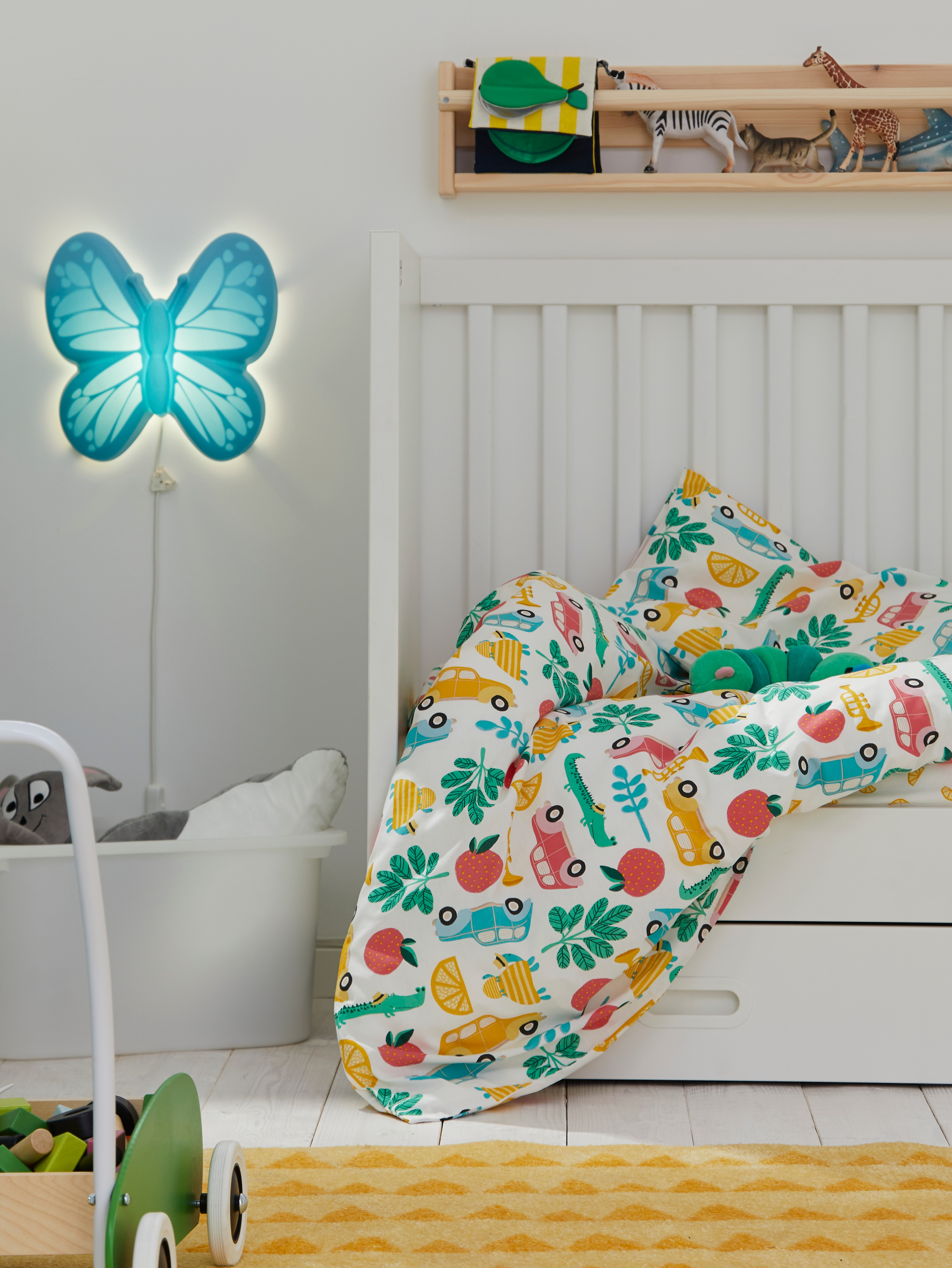 A STUVA/FRITIDS cot with drawers covered in multicolour RÖRANDE bed linen. A blue UPPLYST light is on the wall next to it.