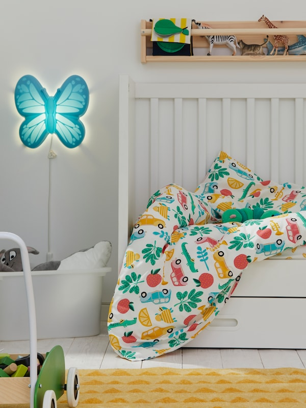 A STUVA/FRITIDS cot with drawers and multicoloured RÖRANDE bed linen. An UPPLYST LED wall lamp sits on the wall nearby.