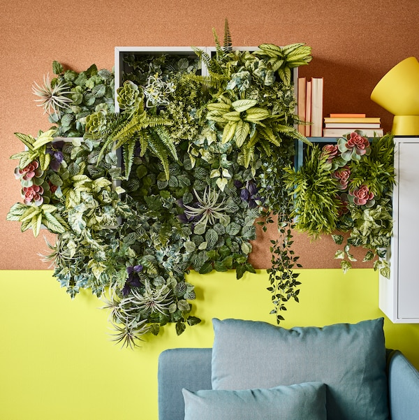 A plant stand with many green plants.