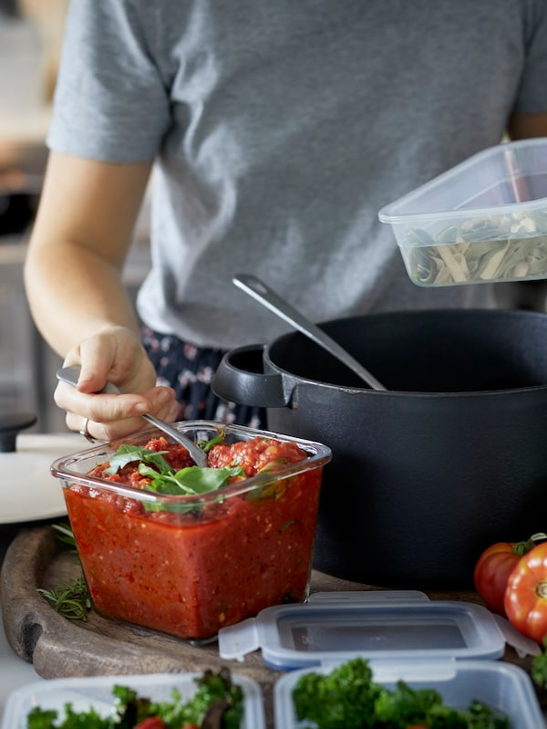 Woman pouring tomato sauce from food storage container into pot
