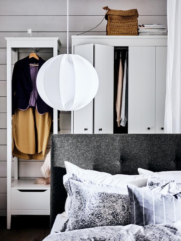 Un cadre de lit IDANÄS blanc surmonté d'une suspension, devant deux armoires-penderies blanches dans lesquelles on voit des vêtements suspendus.