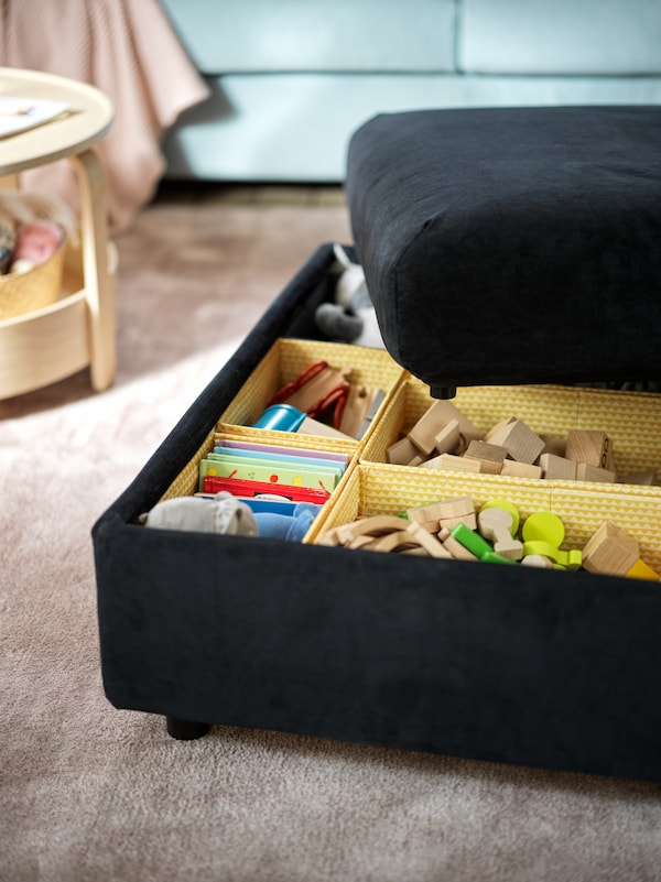 A black-blue VIMLE footstool with its lid half-off, revealing toys sorted in multiple yellow UPPRYMD boxes.