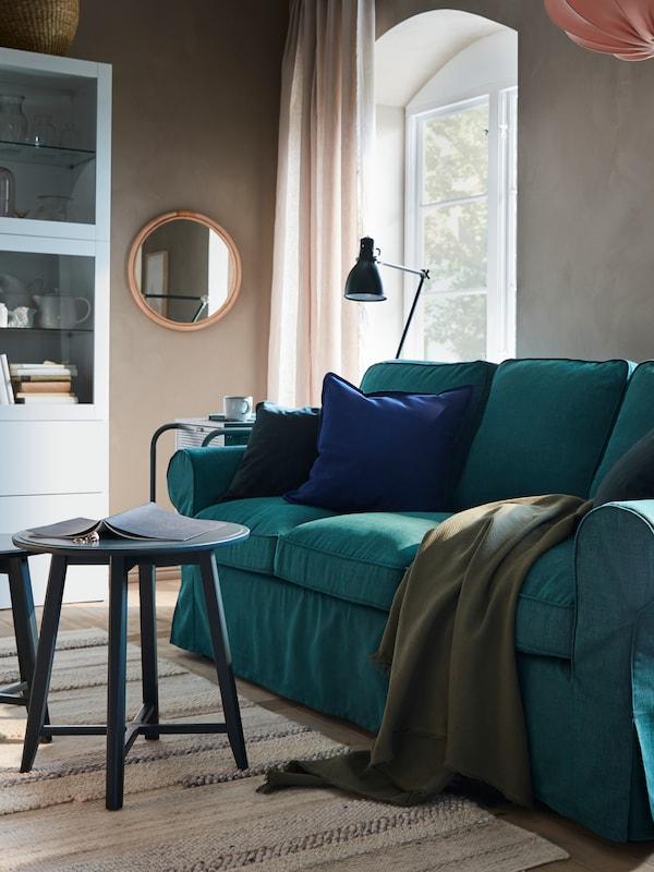 Un sofá de tres plazas en turquesa con una manta sobre él, lámparas de techo y una ventana con cortinas y un espejo detrás.