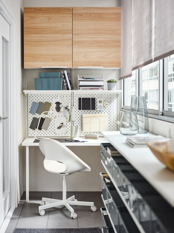 A beige/white swivel chair, a white desk, white pegboards, BOAXEL storage system and shelving, plus white/oak ENHET cabinets.