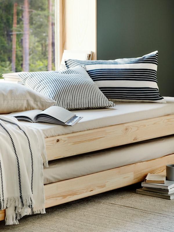 UTÅKER-pinottavasänky ison ikkunan edessä. Sängyllä on METTALISE- ja INGALILL-koristetyynyt, avoin kirja sekä STINAMAJ-huopa. Lattialla on TIPHEDE-matto.