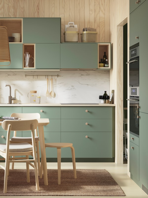 A grey-green BODARP kitchen, a splashback in marble effect, walls in wood panelling and table, stool and chairs in birch.
