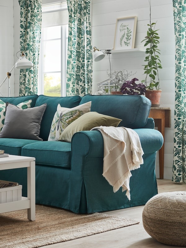 White cotton ODDRUN throw draped over the arm of a green EKTORP sofa with cushions in a living room.