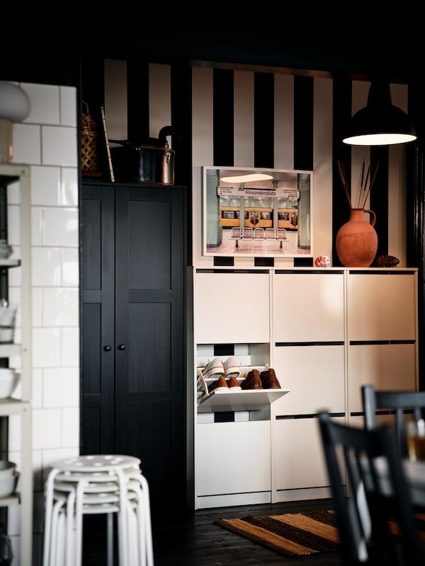 Teil eines schwarz-weiß gestreiften Flurs mit weißen BISSA Schuhschränken und einem schwarzbraunen RAKKESTAD Kleiderschrank.