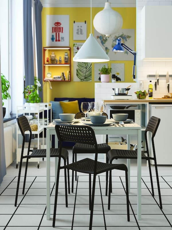 A white dining table with tableware, four black chairs, and a white pendant lamp turned on.