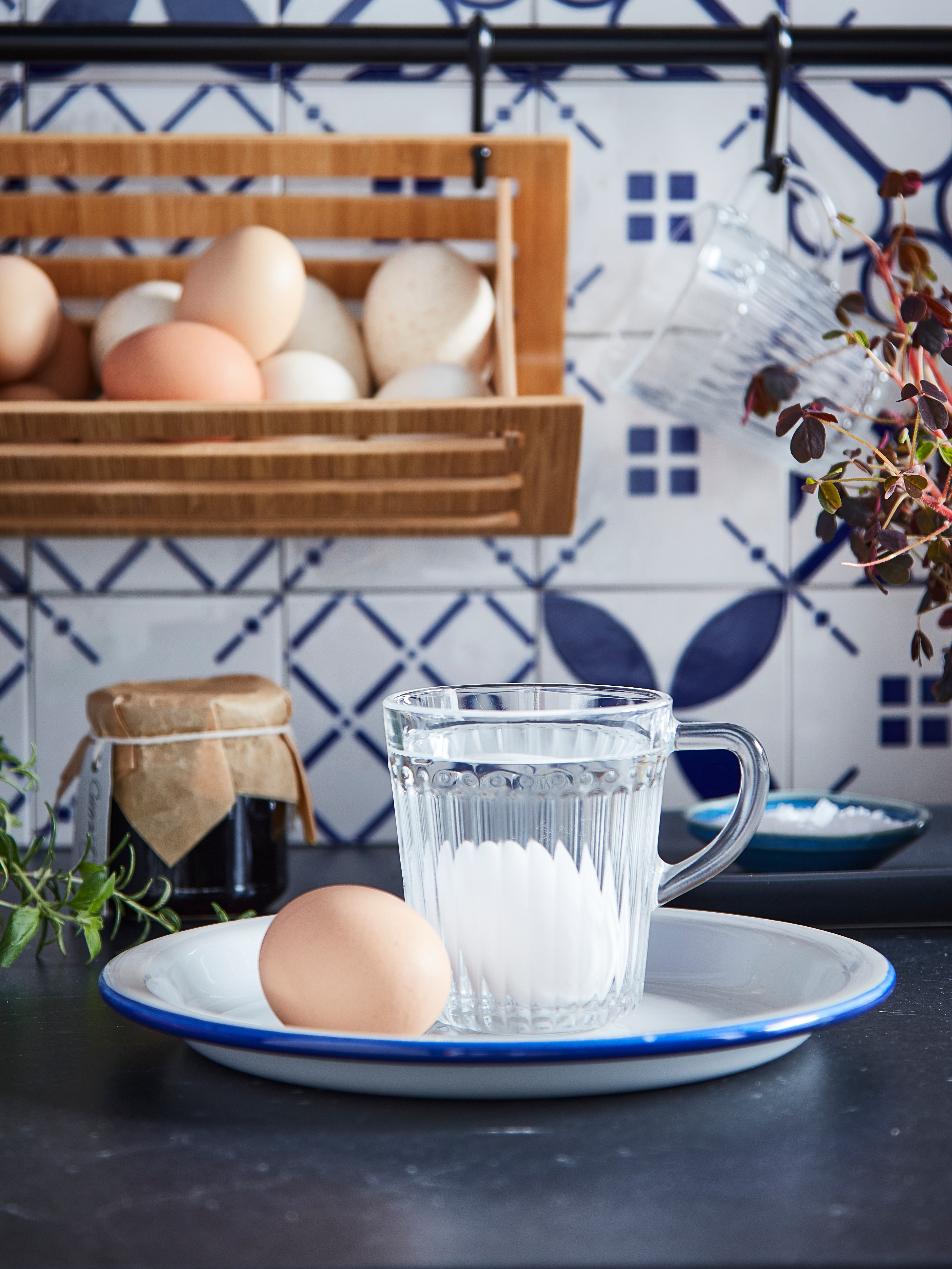 Close-up of a DRÖMBILD mug in clear glass with an egg inside, sitting on a blue and white plate on a kitchen countertop.