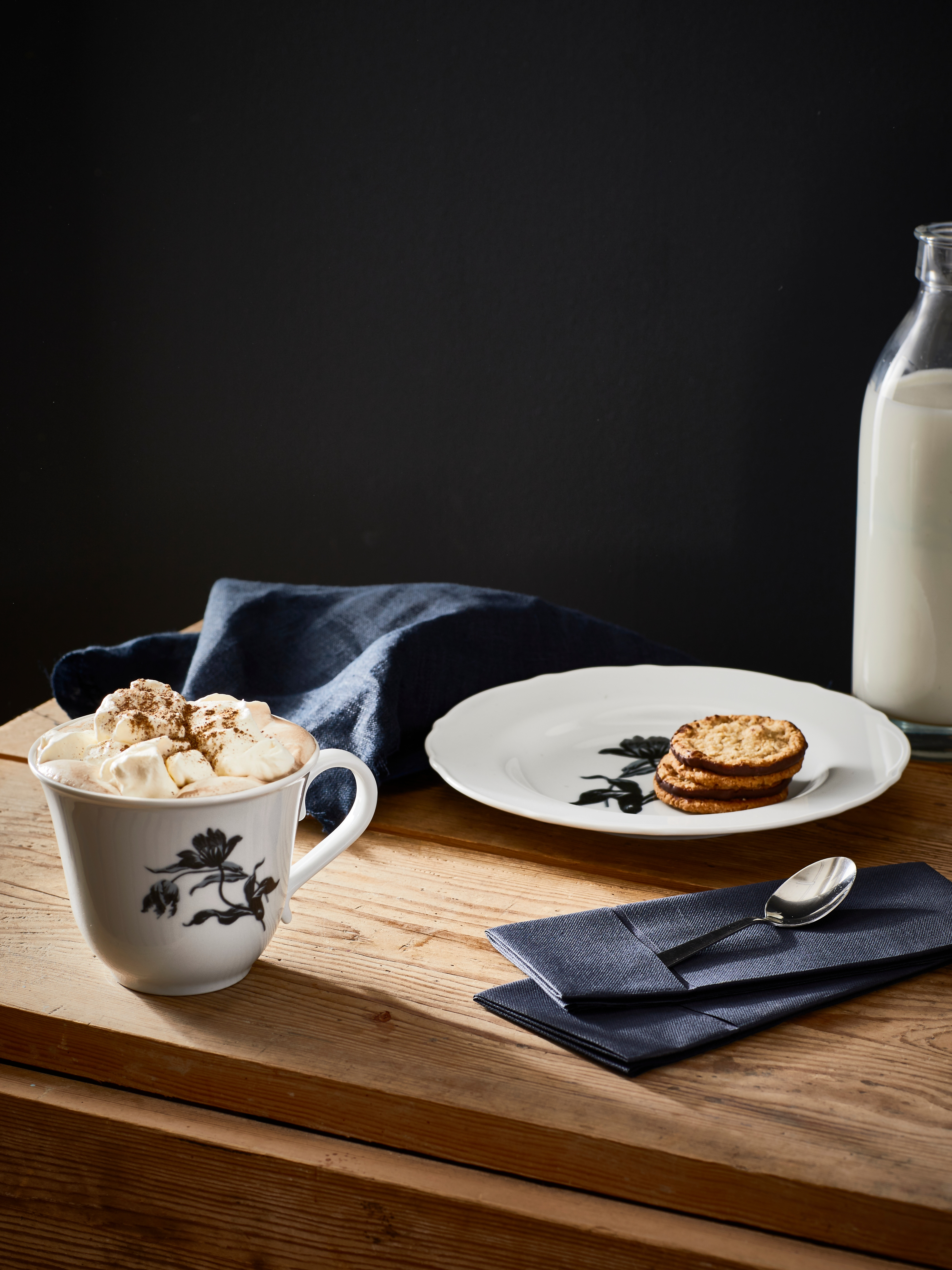 UPPLAGA porcelain cup and saucer set with whipped cream and cookies on a wooden table with milk bottle, spoon and napkins.